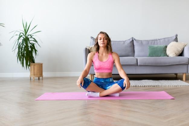 Meditação. ioga em casa - retrato de corpo inteiro de uma mulher.