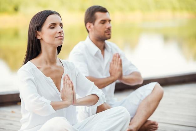 Meditação matinal. lindo casal jovem com roupas brancas meditando juntos ao ar livre e de olhos fechados