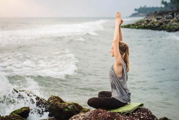 Meditação perto do mar no pôr do sol