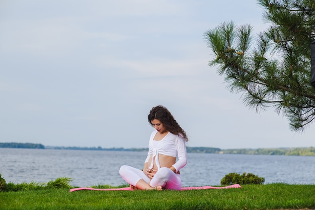 Meditando a mulher grávida ao ar livre.