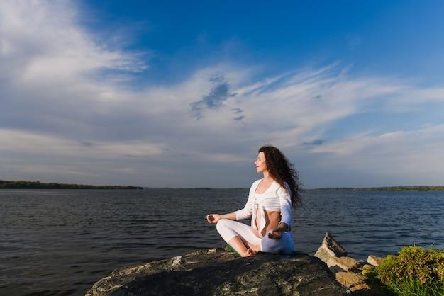 Meditando a mulher grávida em posição de lótus.