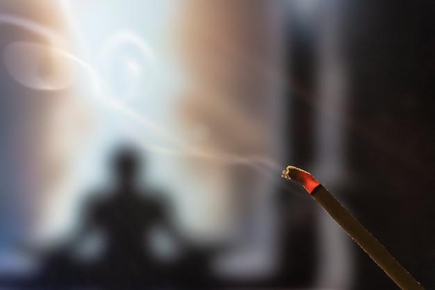 Meditando na posição de lótus. concentre-se em incenso e fumaça. praticante de yoga irreconhecível no.