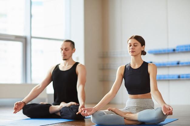 Meditando o casal no estúdio de yoga