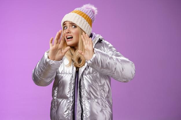 Medo intenso desconfortável jovem loira no chapéu de inverno prata elegante vestido correr levantar as mãos autodefesa virar a cabeça para longe amigo com medo derramar bebida nova roupa, fundo roxo.