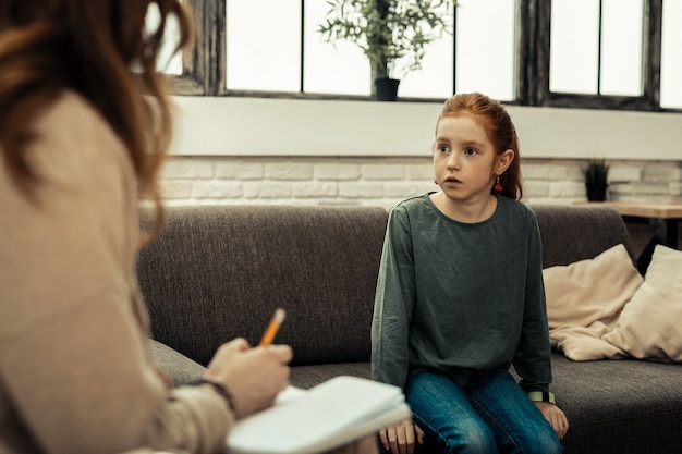 Medos infantis. garota simpática e preocupada sentada na mesa enquanto olha para a psicóloga