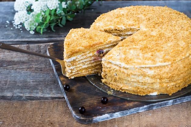 Medovik do bolo de mel do russo na tabela de madeira e no fundo branco. bolo com frutas. bolo de groselha