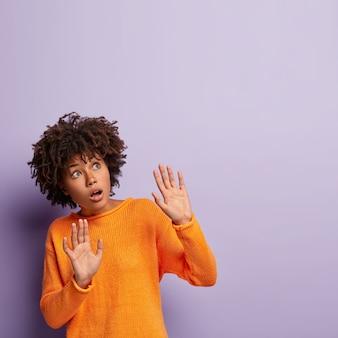 Medrosa fêmea de pele escura mantém as palmas das mãos para frente, tenta se defender, focada no alto, evita algo terrível, usa um macacão laranja, isolada contra a parede roxa. oh não, algo está caindo