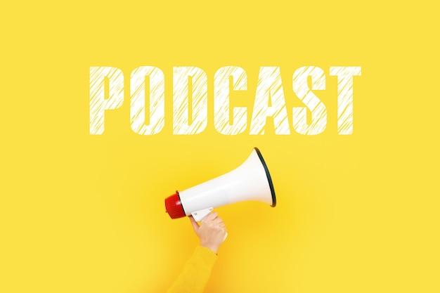 Megafone na mão e podcast de inscrição em uma parede amarela