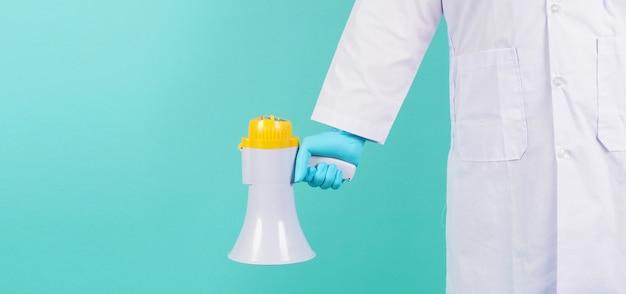 Megafone na mão. homem usa vestido de médico e luva médica azul em fundo verde menta ou azul tiffany. tiroteio em estúdio.
