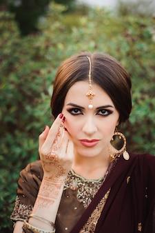 Mehendi nas mãos das meninas, mãos de mulher com tatuagem marrom mehndi.
