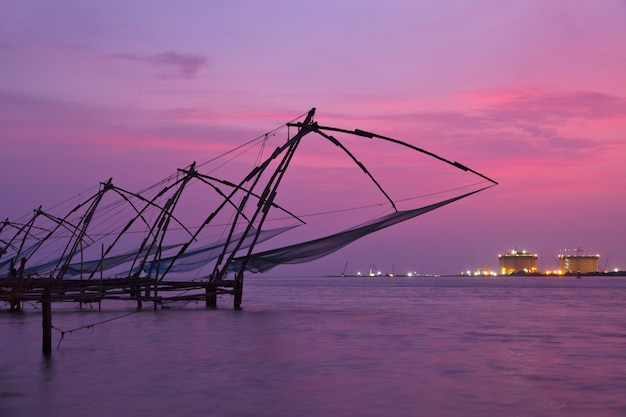 Meia arrastão chinesa no pôr do sol. kochi, kerala, índia