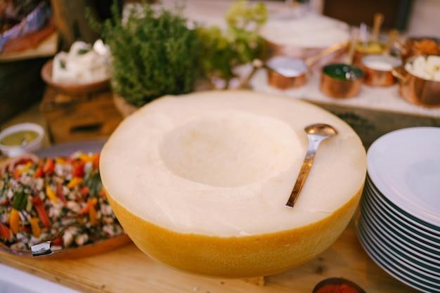Meia bola de queijo em uma mesa de madeira com pratos de colher e salada em uma bandeja de queijo parmesão duro