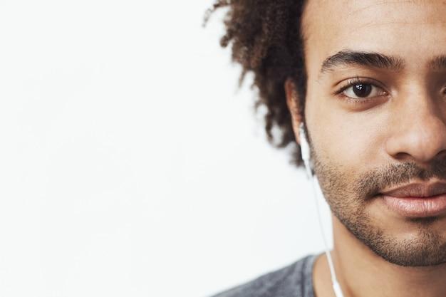 Meia cara fechar retrato do homem africano feliz em fones de ouvido, sorrindo, ouvindo música fumegante.