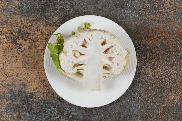 Meia couve-flor no prato, na superfície de mármore