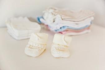 Meia de malha do bebê na frente de fralda e roupas empilhadas