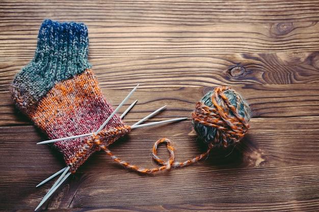 Meia de malha, novelo de lã e agulhas de tricô na superfície de madeira