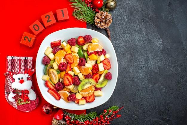 Meia dose da coleção de frutas frescas no prato de jantar acessórios de decoração ramos de abeto e números em um guardanapo vermelho no lado direito sobre fundo escuro