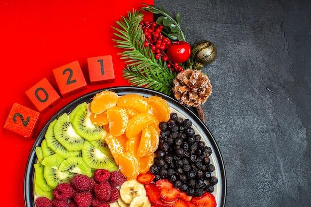 Meia dose da coleção de frutas frescas no prato de jantar acessórios de decoração ramos de abeto e números em um guardanapo vermelho sobre um fundo preto