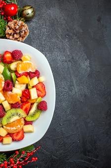 Meia dose da coleta de frutas frescas no prato de jantar acessórios de decoração ramos de abeto em fundo escuro