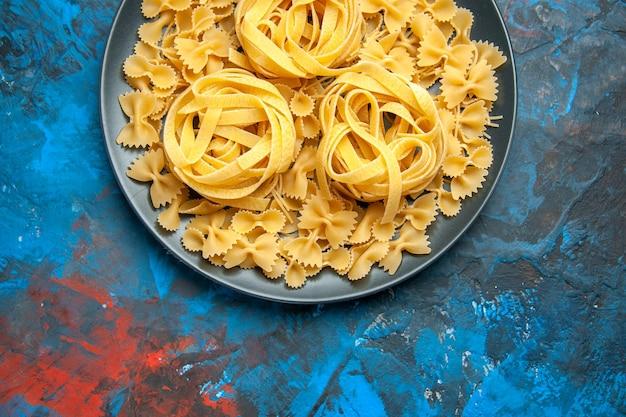 Meia dose da preparação do jantar com macarrão em um prato preto no lado esquerdo sobre fundo azul