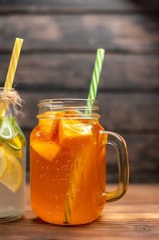 Meia dose de água desintoxicante fresca e suco de frutas servida com tubos no lado esquerdo em um fundo marrom