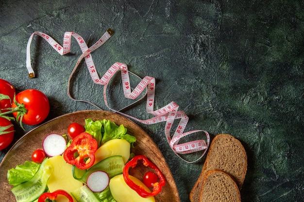 Meia dose de batatas frescas descascadas com rabanetes de pimenta vermelha e tomates verdes em um prato marrom e mede as fatias de pão de especiarias em uma superfície de cores pretas e verdes