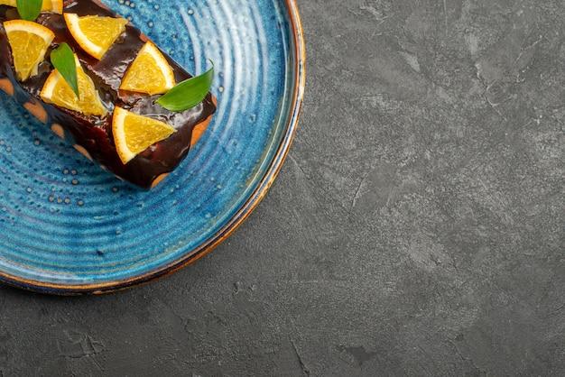 Meia dose de bolo macio decorado com laranja e chocolate na mesa escura