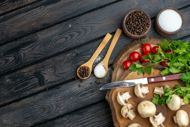 Meia dose de cogumelos frescos e especiarias de tomate faca na toalha de tábua de madeira em fundo preto