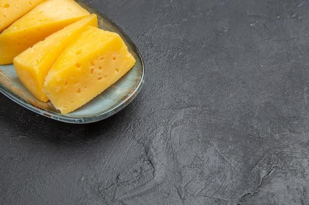 Meia dose de deliciosos queijos amarelos fatiados em um prato azul no lado direito sobre fundo preto