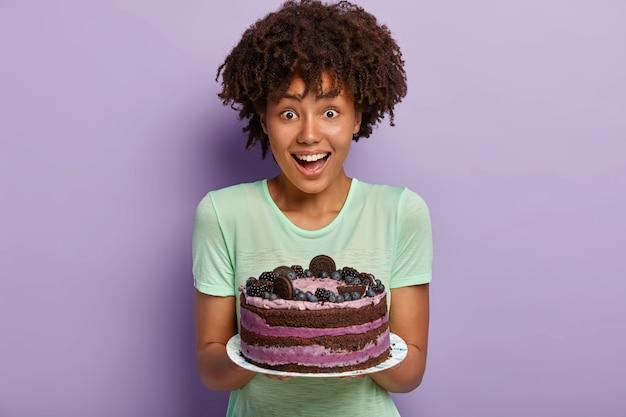Meia dose de dente doce feminino com cabelo afro, segurando um delicioso bolo doce no prato