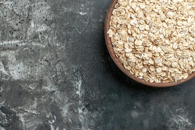 Meia dose de farelo de aveia orgânico em uma panela de madeira marrom em fundo escuro