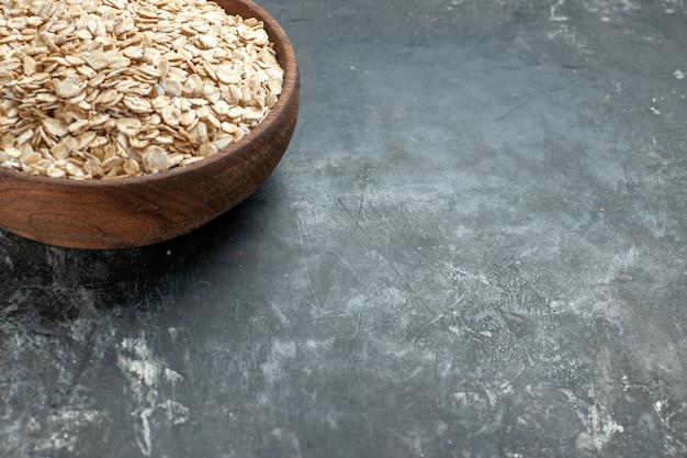 Meia dose de farelo de aveia orgânico em uma panela de madeira marrom no lado direito em fundo escuro