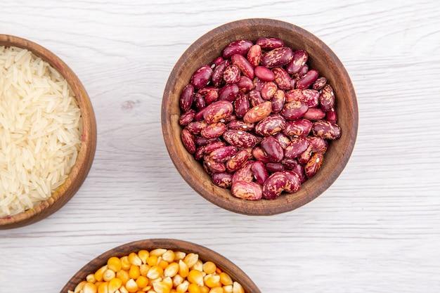Meia dose de feijão fresco e arroz, grãos de milho, lentilhas amarelas em tigelas marrons na mesa branca na vista acima