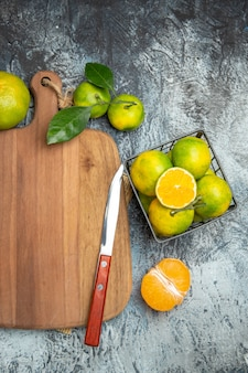 Meia dose de frutas cítricas frescas com folhas na tábua de madeira cortadas ao meio e faca na mesa cinza do jornal