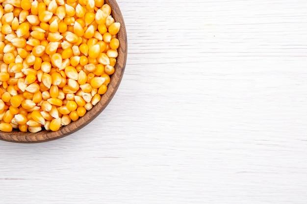 Meia dose de grãos de milho frescos em uma tigela marrom na mesa branca