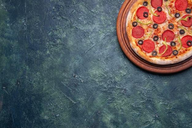 Meia dose de pizza deliciosa em uma tábua de madeira no lado esquerdo em uma superfície azul escura com espaço livre