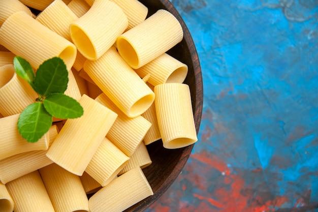 Meia dose de preparação do jantar com macarrão macarrão com verde em uma panela marrom sobre fundo azul