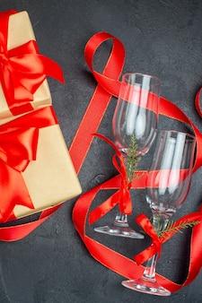 Meia dose de presentes bonitos e taças de vidro em fundo escuro