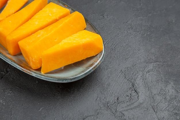 Meia dose de queijo fresco fatiado em amarelo em um prato azul do lado direito sobre um fundo preto