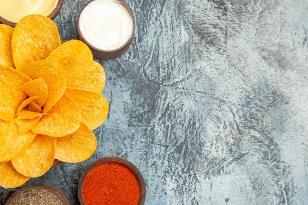 Meia dose de saborosas batatas fritas decoradas em forma de flor e especiarias diferentes na mesa cinza
