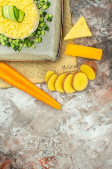 Meia dose de salada saborosa em um jornal velho e dois tipos de queijo e batata cenoura picada em mesa de cores mistas