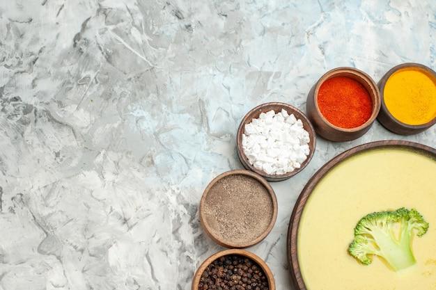 Meia dose de sopa cremosa de brócolis em uma tigela marrom e temperos diferentes na mesa cinza