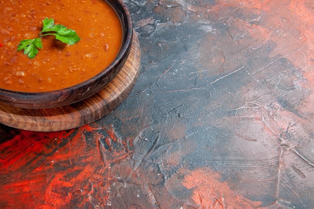 Meia dose de sopa de tomate em uma tábua de corte marrom em uma mesa de cores variadas