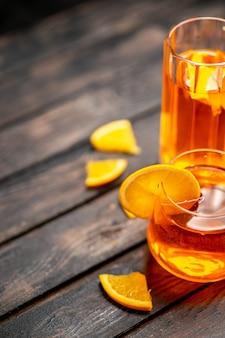 Meia dose de suco fresco natural delicioso em dois copos com limas de frutas no fundo preto