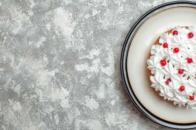 Meia dose de um delicioso bolo cremoso decorado com frutas no lado esquerdo em um fundo de gelo