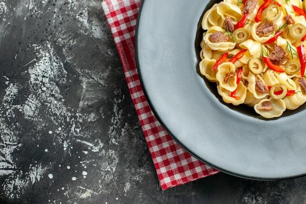 Meia dose de uma deliciosa conchiglie com legumes em um prato e uma faca em uma toalha vermelha despojada sobre fundo cinza