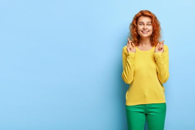 Meia dose de uma feliz e esperançosa fêmea de gengibre desejando e antecipando algo