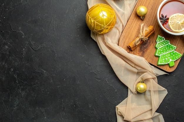 Meia dose de uma xícara de chá preto com limão e limão e canela, acessórios de decoração de natal em uma tábua de madeira