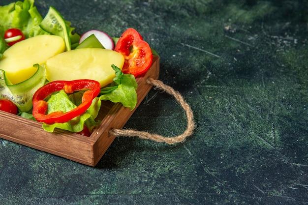 Meia dose de vegetais frescos picados em uma bandeja de madeira em uma superfície de mistura de cores com espaço livre