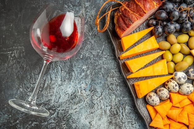 Meia dose do melhor lanche saboroso em uma bandeja marrom e uma taça de vinho caída no fundo de gelo